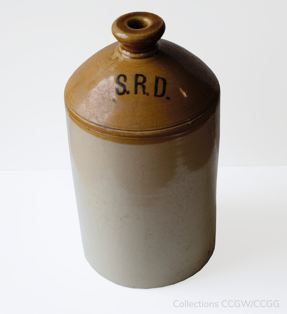 a brown ceramic jug with the letters S.R.D. printed on it