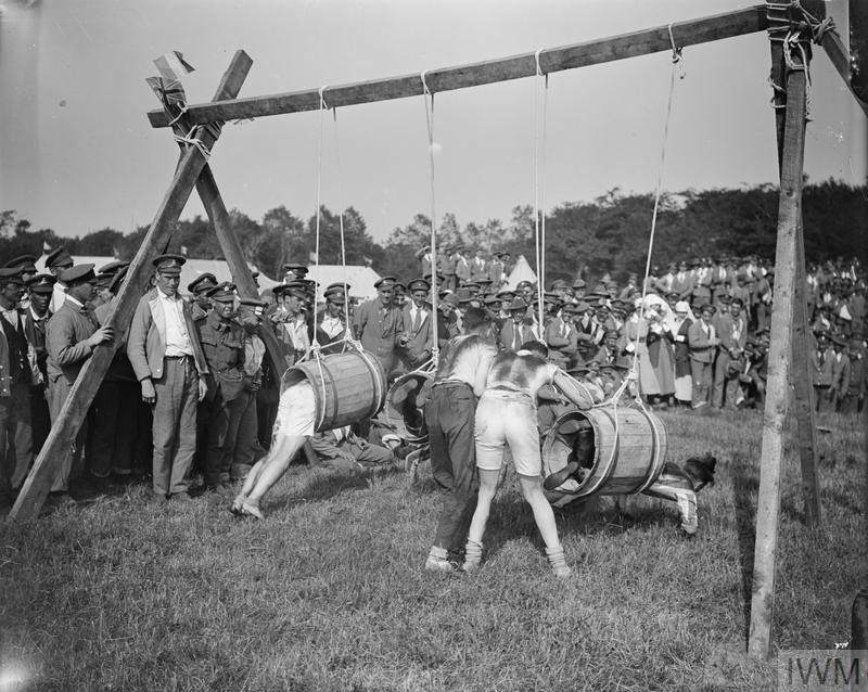 men climbing into hanging barrels