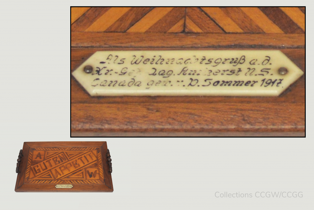 Two part composite image. In the bottom-left: a shrunk photo of the entire 'Guten Appetit' decorative tray. In the top right: A zoomed in view of the inscription which can be found on a plaque attached to the bottom of the tray.