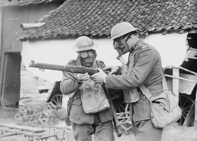 Two soldiers wearing gas masks examining a Lee Enfield rifle